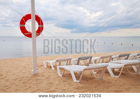 Life Ring Hanging On A Pillar And Sun Beds On The Beach Against The Sea