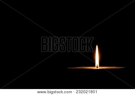 A Glowing Candle On The Dark Background
