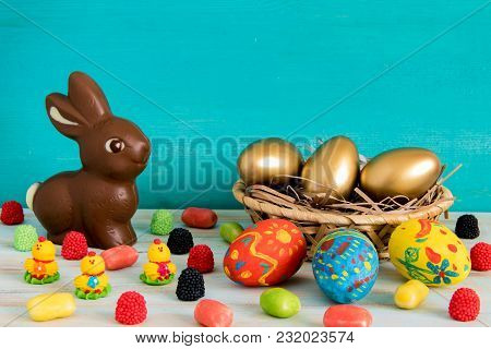 Easter Conceptual Image On Blue Wooden Background With Copyspace Chocolate Easter Rabbit, Candy, Swe