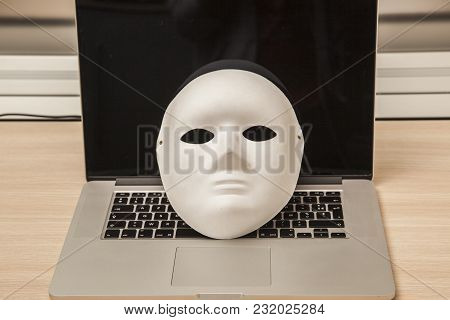 Conceptual Photo, Mask On A Laptop As A Symbol Of A Hacker Attack, Front View