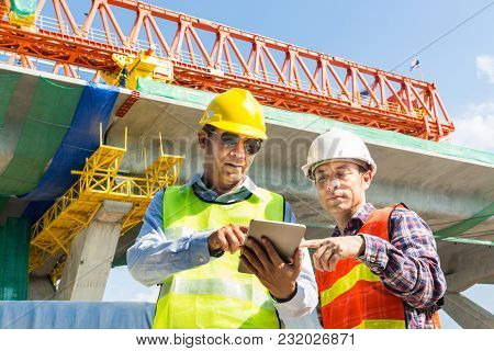 Male Architect And Engineer Working Together With Digital Wireless Tablet Beside Autobahn Or Express