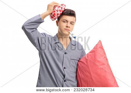 Sick teenage boy in pajamas holding an icepack on his head and a thermometer in his mouth isolated on white background