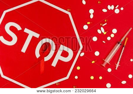 Red Tape As Symbol Of Aids / Hiv Illness Lying With Red Stop Road Sign, Medicine Drugs And Syringe I