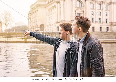Two Male Tourists Exploring Government District With Reichstag Building And Spree River In Berlin Ge