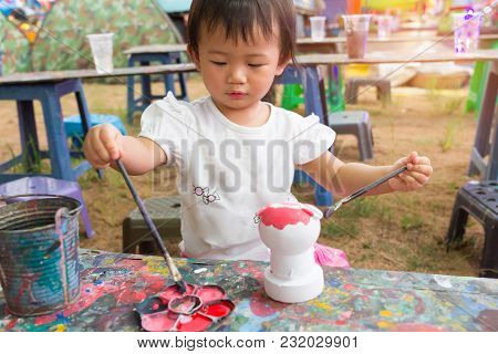 Asian Cute Girl Baby Is Painting Colorful In The Park.