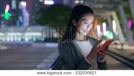 Woman looking at mobile phone in the evening