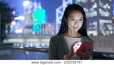 Woman looking at smart phone in city at night