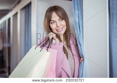 Young girl with shopping bags in dressing room