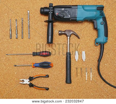 Hand Tools Laid Out On The Desktop. Drill, Hammer, Screwdrivers, Pliers And Hardware. Flat Lay, Top