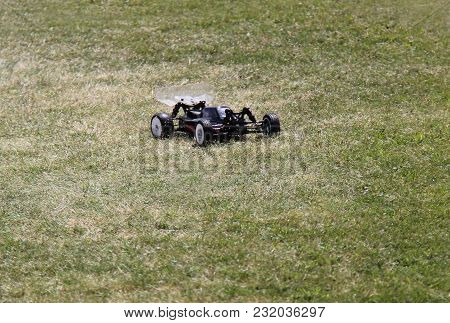 A Radio Controlled Fast Racing Car On A Grass Track.