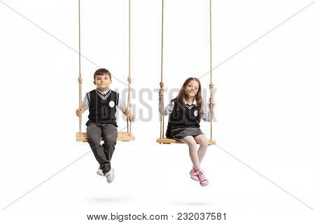 Schoolboy and a schoolgirl sitting on wooden swings isolated on white background