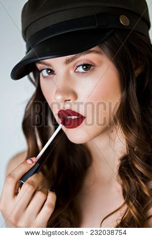 Young Woman Applying Red Lip Gloss Close Up. Beauty Cosmetics