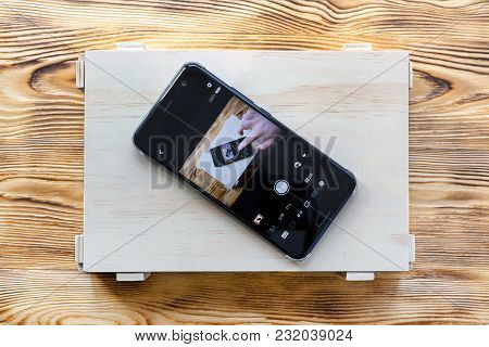 Smartphone On A Wooden Box With Itself Image On Screen. Remote Camera Control Application Concept.
