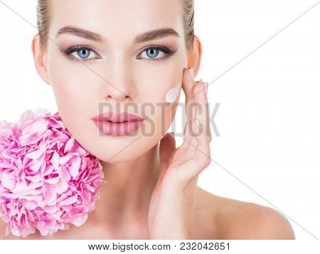 Young woman touches cheek by fingers. Young beautiful woman with flowers near face. Beauty treatment concept. Skin care. Pretty female with health, fresh skin of body. Lady with pink makeup of eyes.