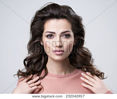 Portrait of brunette woman with beautiful long brown hair.  Pretty young adult girl posing at studio. Closeup attractive female face.
