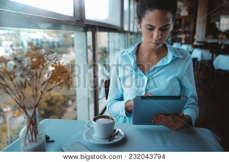 A Pensive Young Woman Entrepreneur In A Teal Shirt Is Sitting At The Table In A Luxury Restaurant Du
