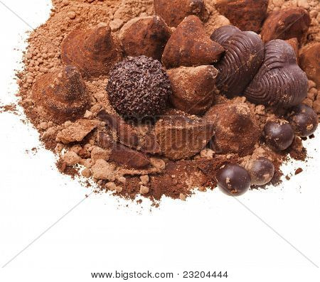 cocoa powder with chocolate truffles isolated against white background
