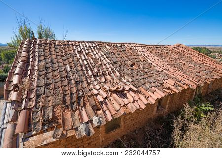 Roof Of Building Depressed With Old Clay Tiles Broken And Blue Sky