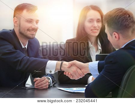 handshake financial partners sitting at the table