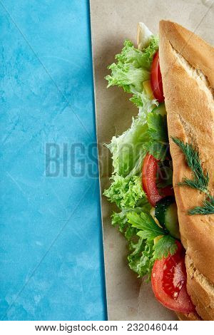 Fresh And Tasty Submarine Sandwich With Cheese, Lettuce And Vegetables On Paper Plate Over Light Blu