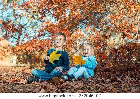 Two Smiling Kids Sitting On The Ground And Holding Maple Leaves In Autumn Park