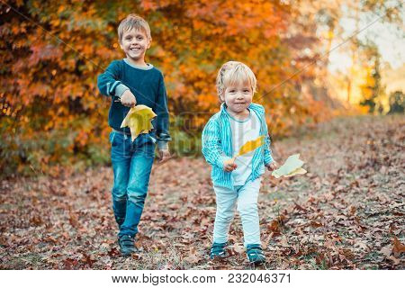 Two Smiling Playing With Maple Leaves In Autumn Park, South Australia