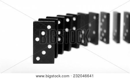 Curved Row Of Black Wooden Dominoes Standing On A White Background. Logical Game. Business Concept.