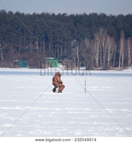 A Man Catches Fish On Ice In Winter .