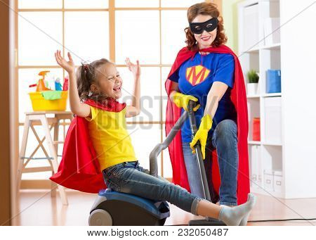 Child And Mom Dressed As Superheroes Using Vacuum Cleaner In Room. Family - Woman And Kid Daughter H