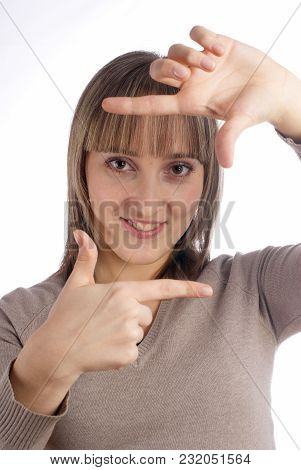 Young Woman In Sweater Showing Frame By Hands Over White Background