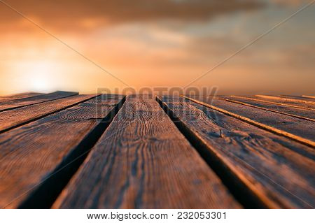 Horizontal Shot. Close Up Top Wooden Table And Blur Sunset Background. Tonted Orange.