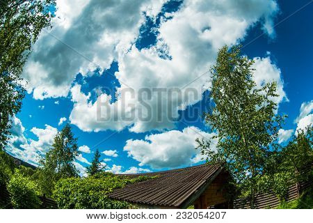 Blue Sky With Clouds And Treetop In Sunny Day