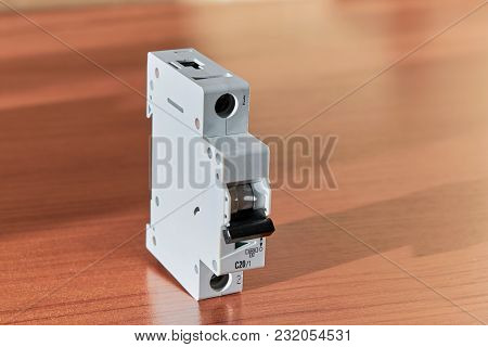 On The Wooden Table Is A Modern Modular Circuit Breaker. The Switch Has A Status Indication On Or Of