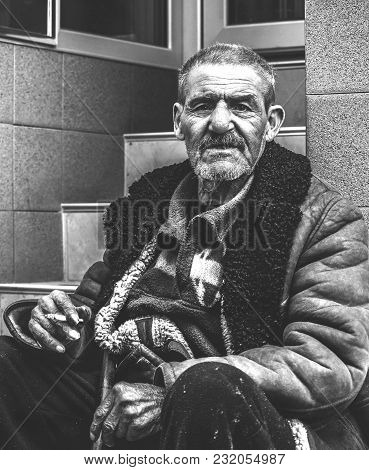Homelessness Concept. Old Poor And Homeless Gypsy Man Sitting On The Stairs On The Street Smoking Ci