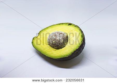 Half Of Black Ripe Avocado On White Background