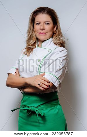 Studio Portrait Of A Beautiful Woman Chef In Uniform. A Happy, Smiling Woman Cook In A Uniform On A