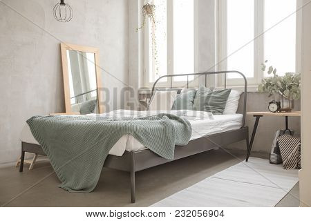 Bed With Green Coverlet Stands In Bright Bedroom With Large French Windows Mirror And Small Bedside