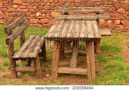 Tables And Chairs Typical Of Previous Centuries In A Picturesque Village With Its Black Slate Roofs