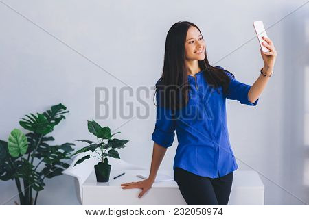 Young Attractive Woman Doing Selfie At Her Workplace For Her Profile In Social Networks. Good News,