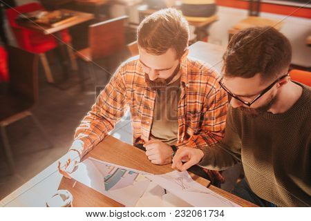 Close Up Of Two Adult And Bearded Guys Sitting At The Table And Studying Graphics In Documents. They
