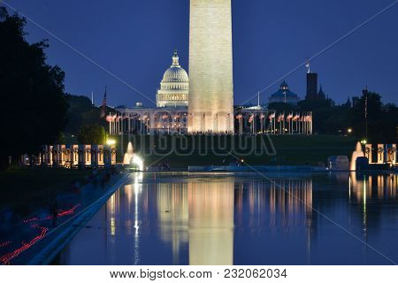 Washington DC at night - National Mall view including the Capitol and Washington Monument and World War II Memorial with the reflection on the reflection pool.