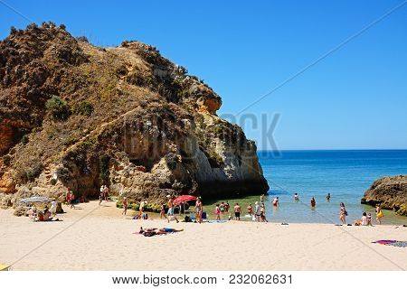 Portimao, Portugal - June 7, 2017 - Tourists Relaxing On The Beach By Two Large Rocks With Views Acr