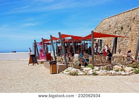 Sagres, Portugal - June 9, 2017 - Tourists Relaxing At A Covered Pavement Cafe, Cape St Vincent, Sag