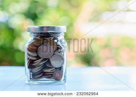 Coins In Glass Jar Against Blurred Natural Green Background And Copy Space For Investment, Business,