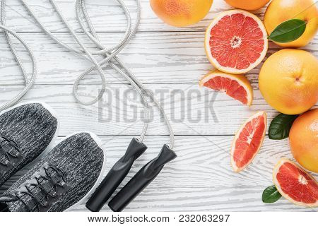 Sport Shoes, Rope And Fresh Grapefruits On Rustic White Wooden Table, Fitness Accessories. Concept O