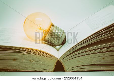 Opened Book With Glowing Light Bulb On Dark Background, Added Colour Filter And Classic Tone Effect