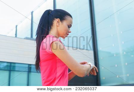 Young And Sporty Girl With A Smartwatch. Sport, Fitness And Healthy Lifestyle Concept.