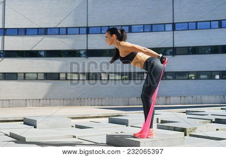 Young And Sporty Girl Training With Elastic Band Outdoor. Resistance Training Concept.