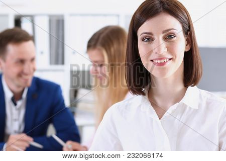 Beautiful Smiling Cheerful Girl At Workplace Look In Camera With Colleagues Group In Background. Whi