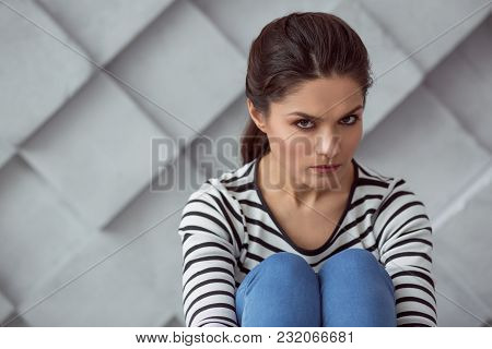 Sadness And Depression. Unhappy Cheerless Attractive Woman Sitting And Looking At You While Sufferin